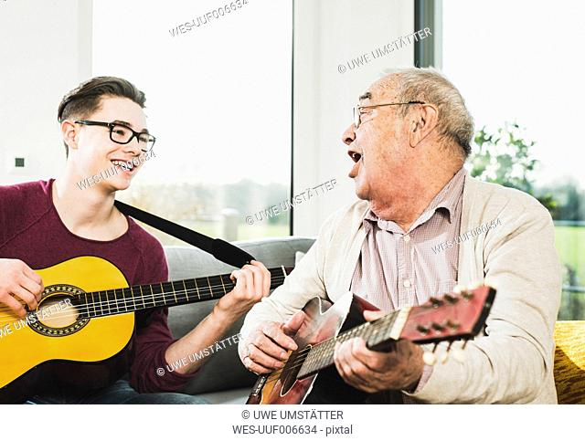 Senior man singing and playing guitar with his grandson