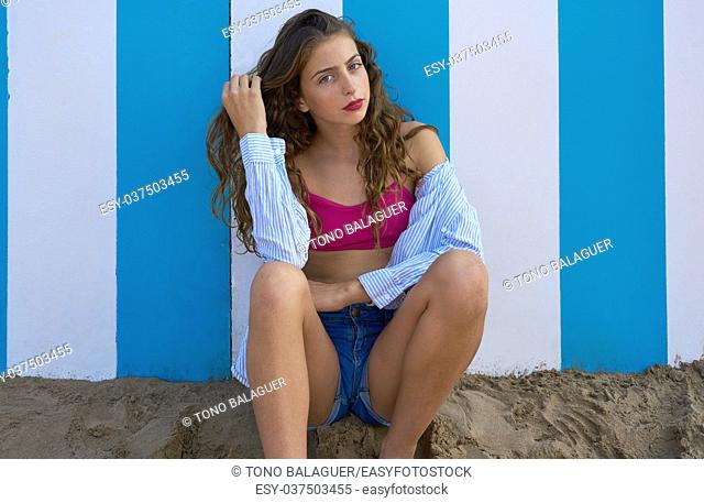 Brunette teen summer girl in a blue stripes wall background
