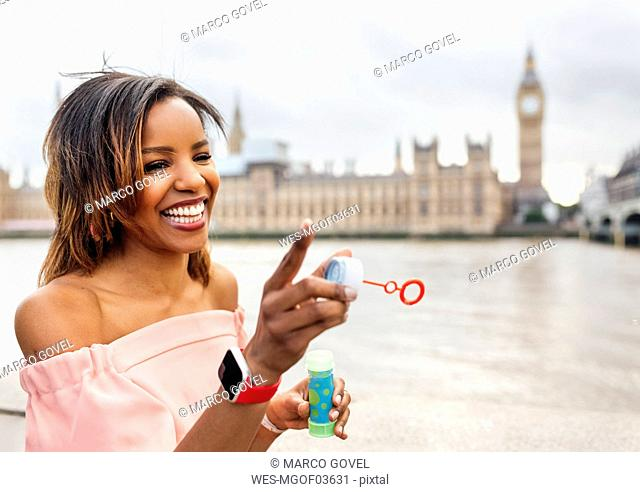 UK, London, happy woman making soap bubbles near Palace of Westminster