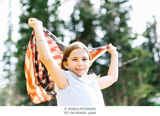Girl (8-9) holding us flag in forest