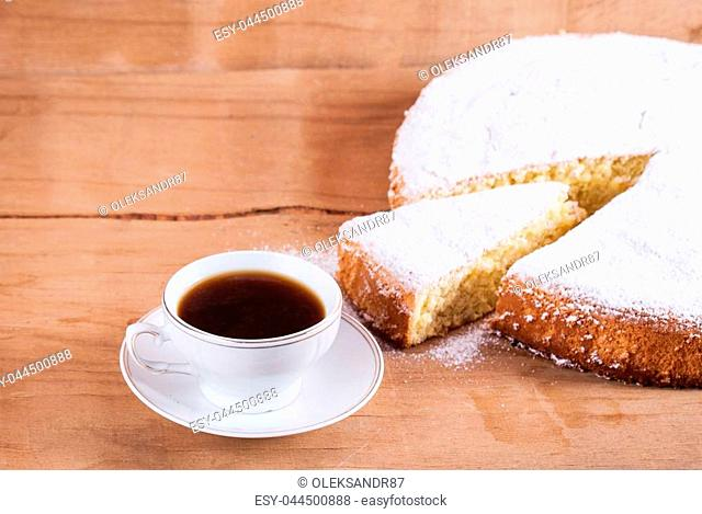Biscuit cake with sugar on wood desk. Home baking. Coffee cup