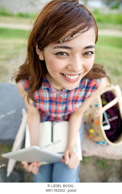 Young woman with a digital tablet in the park