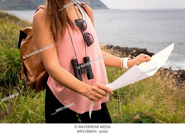 Woman looking at map in countryside