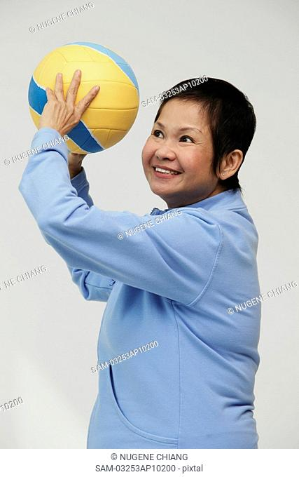 Mature woman throwing a volleyball