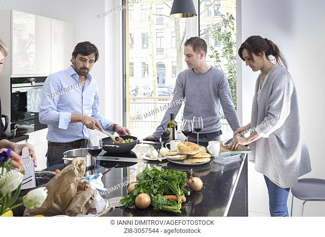 Group of friends preparing vegetarian food together while laughing and enjoying themselves in the kitchen