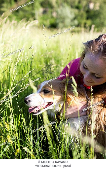 Italy, Lecco, teenage girl with her dog on a meadow