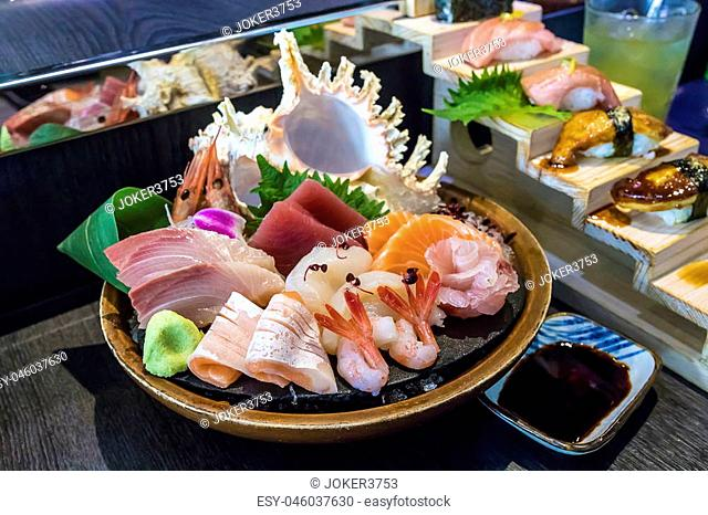selective focus decorated sashimi set in a bowl with ice and conch shell another sushi set behind