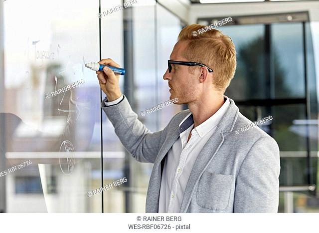 Businessman writing on glass pane in office
