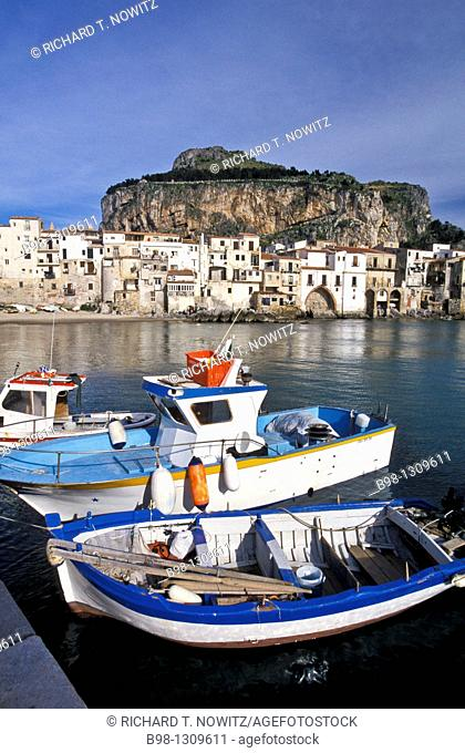 Cefalu, Sicily, Italy  Fishing harbor of the medieval town in late afternoon light  Boats tied to dock  Village and giant rock 'la rocca' in background...