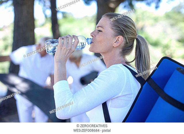 Woman with gym mat drinking water from bottle