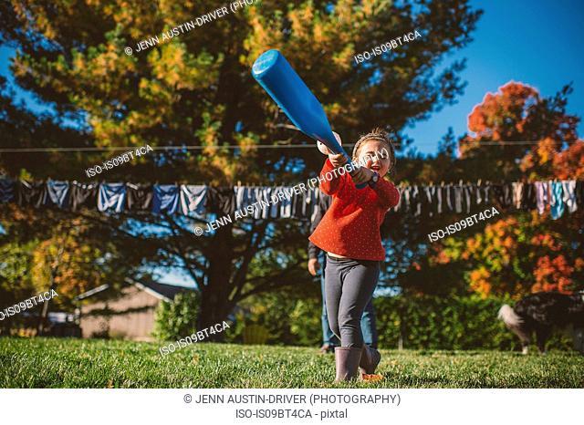Girl swinging baseball bat in garden