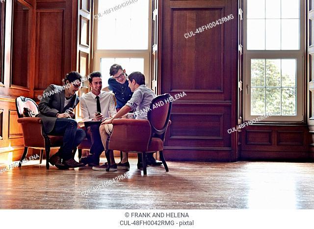 Businessmen talking in ornate room