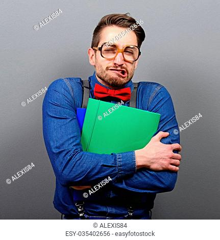 Portrait of a nerd holding books with retro glasses against gray background