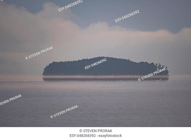 Island Appearing out of the Morning Fog on Saganaga Lake in Quetico Provincial Park in Ontario