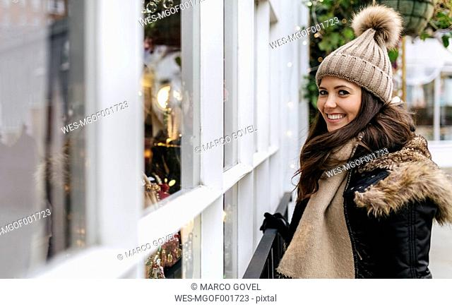 UK, London, Notting Hill, portrait of happy young woman beside window display