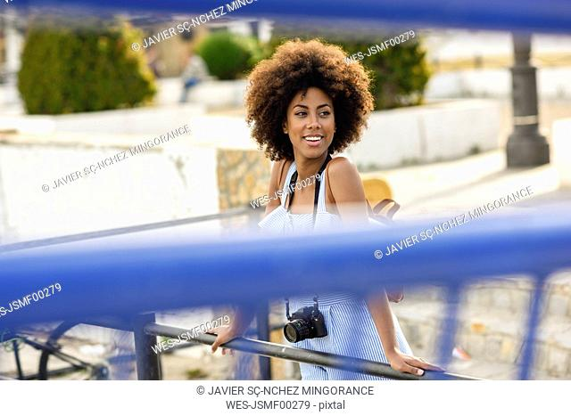 Portrait of smiling young woman with curly hair on a bridge