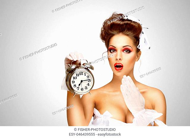 Sexy pinup bride in a vintage wedding corset holding a retro alarm clock on grey background