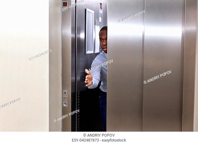 Young African Man Trying To Stop Elevator Door With His Hand