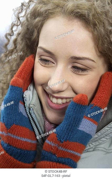 Person holding the face of a young woman carefully with gloved hands, close-up