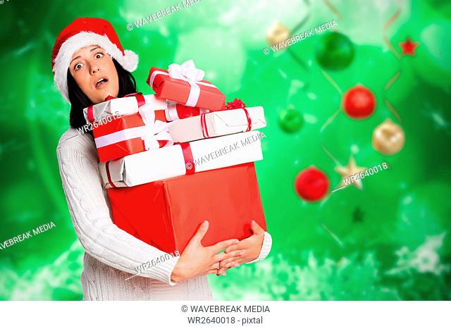 Surprised woman in santa hat holding stack of christmas gifts