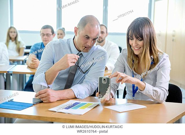 Businessman and woman using smartphone in training class