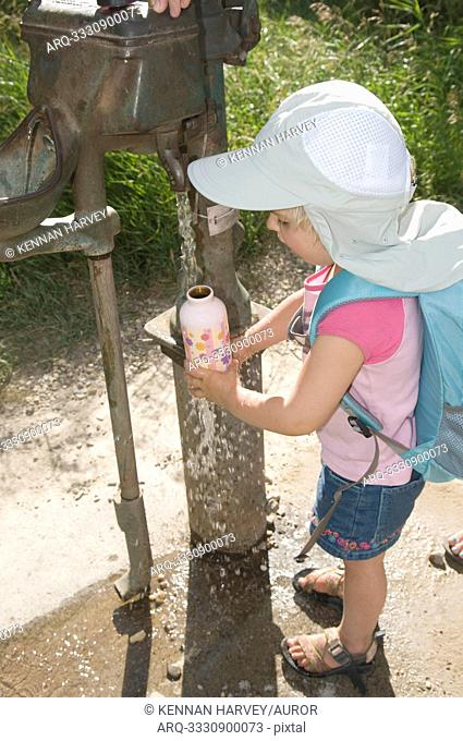 A young girl filling a water bottle from a hand pump while hiking, Almo, Idaho