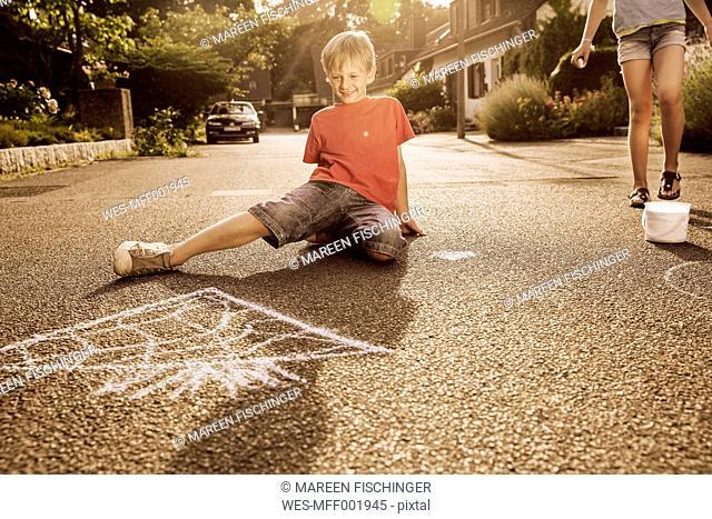 Children using sidewalk chalk in their neighborhood