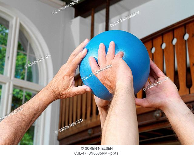 Close up of men passing rubber ball
