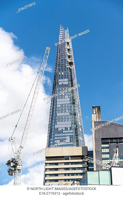 UK, England, London. A construction crane reaching up to the Shard, formerly know as London Bridge Tower, is a 95-storey skyscraper in the Southwark district