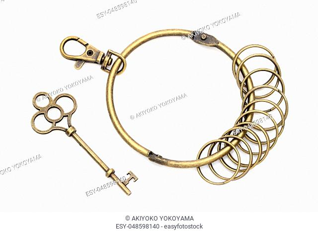 brass key ring with antique golden key on a white background
