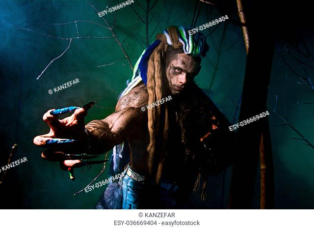 Muscular werewolf with dreadlocks with long nails among the branches of the tree and smoke. Gothic image of scary diabolical creatures for Halloween