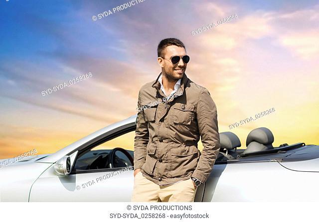 happy man near convertible car over sky