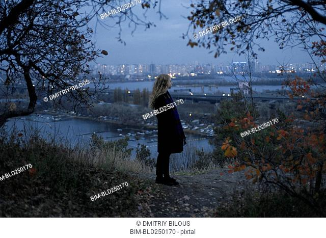 Pensive Caucasian woman standing near urban waterfront at night
