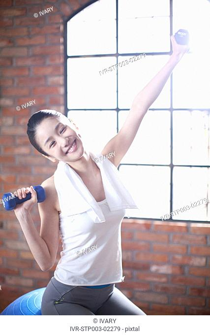 Asian Woman Holding Dumbbells