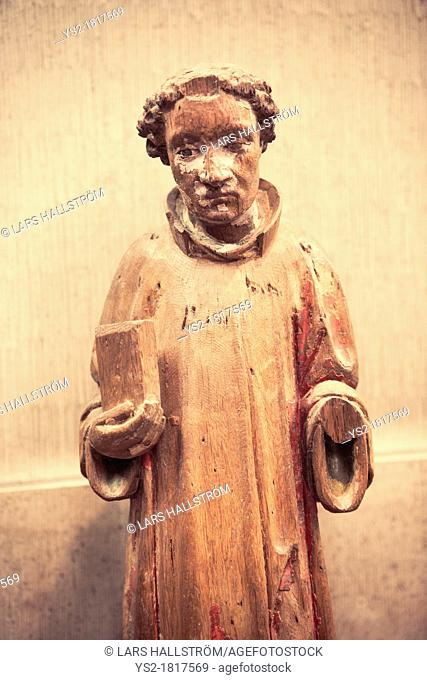 Ancient statuette made in wood of pensive monk