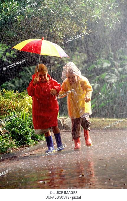 Children in raincoats sharing umbrella