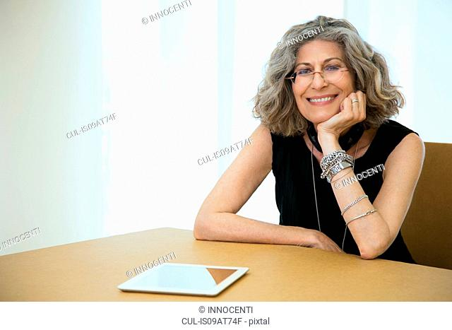 Portrait of senior female designer with digital tablet at boardroom table