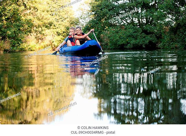 Smiling couple kayaking in creek