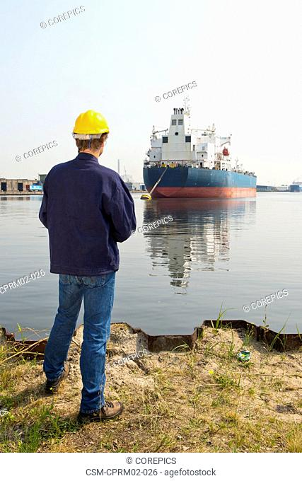 Docker examining an industrial ship, standing on the waters' edge in an industrial harbor