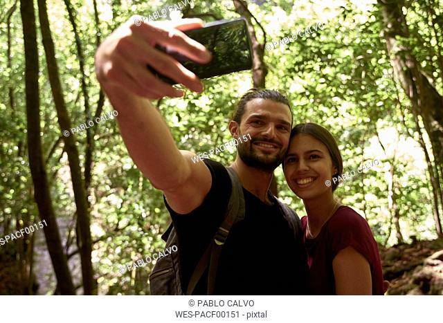 Spain, Canary Islands, La Palma, smiling couple taking a selfie in a forest