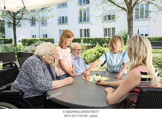 Multi-generation family playing board game at nursing home