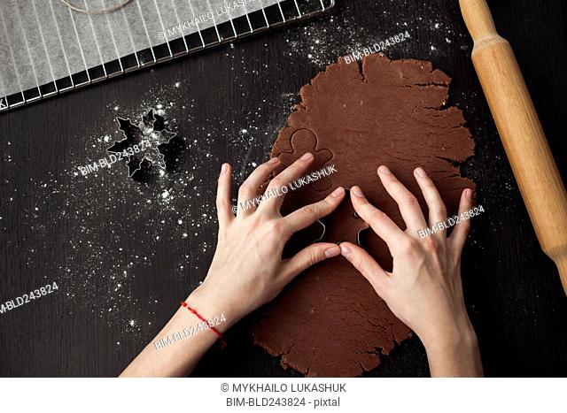 Hand of Caucasian woman pressing pastry cutter into dough