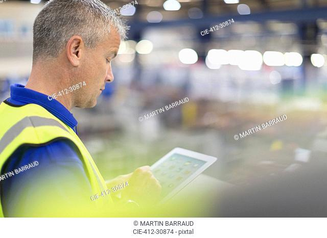 Supervisor using digital tablet in steel factory