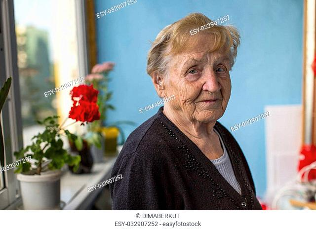 An old woman stands on her balcony