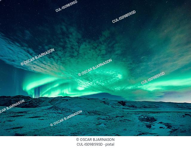 Aurora borealis swirling green over snow covered landscape, Lake Kleifarvatn, Iceland