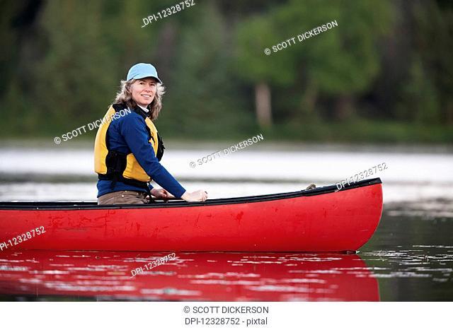 A Woman Canoeing On Stone Step Lake; Homer, Alaska, United States Of America