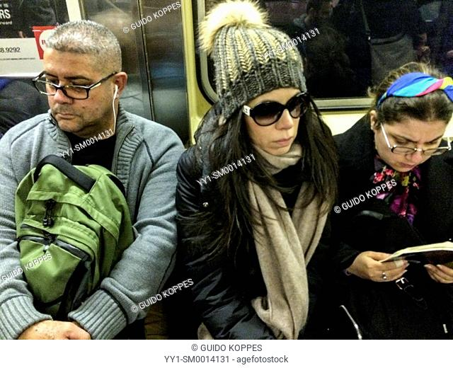 Subway, New York, USA. Three people commuting by subway through Manhattan, while being closely seated together