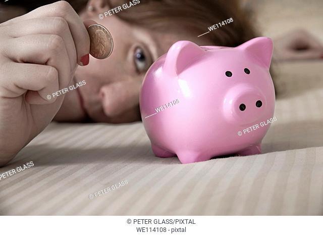 Woman putting an American quarter into a piggy bank