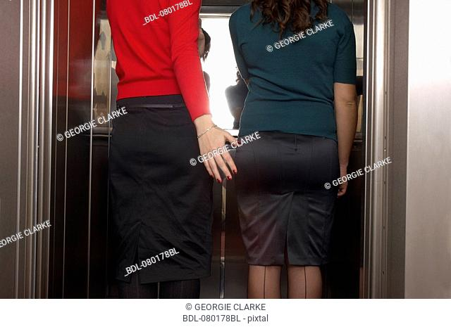 rear view of two businesswomen standing in elevator one hitting her colleague on the bottom