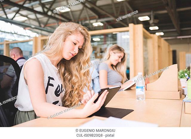 Co-workers working on digital tablet in open plan office